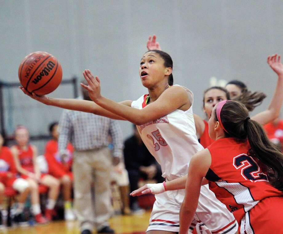 At left, Jayla Faison of Greenwich High's splits a pair of Brien McMahon defenders to score on a driving layup during the Cardinals' 56-43 victory over the Senators in Greenwich on Friday. Photo: Bob Luckey Jr. / Hearst Connecticut Media / Greenwich Time