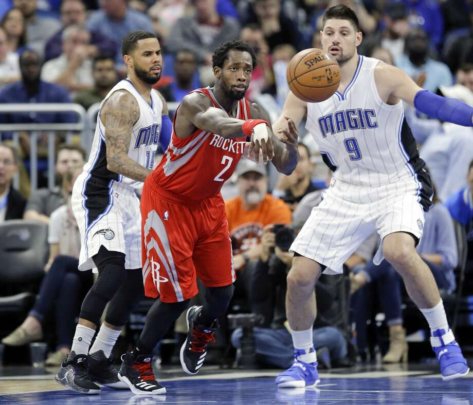 Houston Rockets' Patrick Beverley (2) passes the ball as he is guarded by Orlando Magic's D.J. Augustin, left, and Nikola Vucevic (9) during the second half of an NBA basketball game, Friday, Jan. 6, 2017, in Orlando, Fla. (AP Photo/John Raoux) Photo: John Raoux/Associated Press