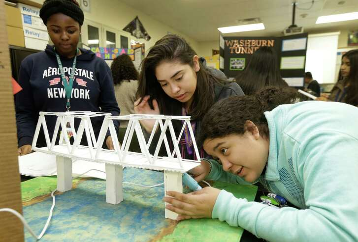 Quaniesha Stephens, 17, left, Asceneth Flores, 15, and Genesis Terrazas, 15, work on a bridge project at Alief Early College High School, one of a handful of schools that received straight A's.