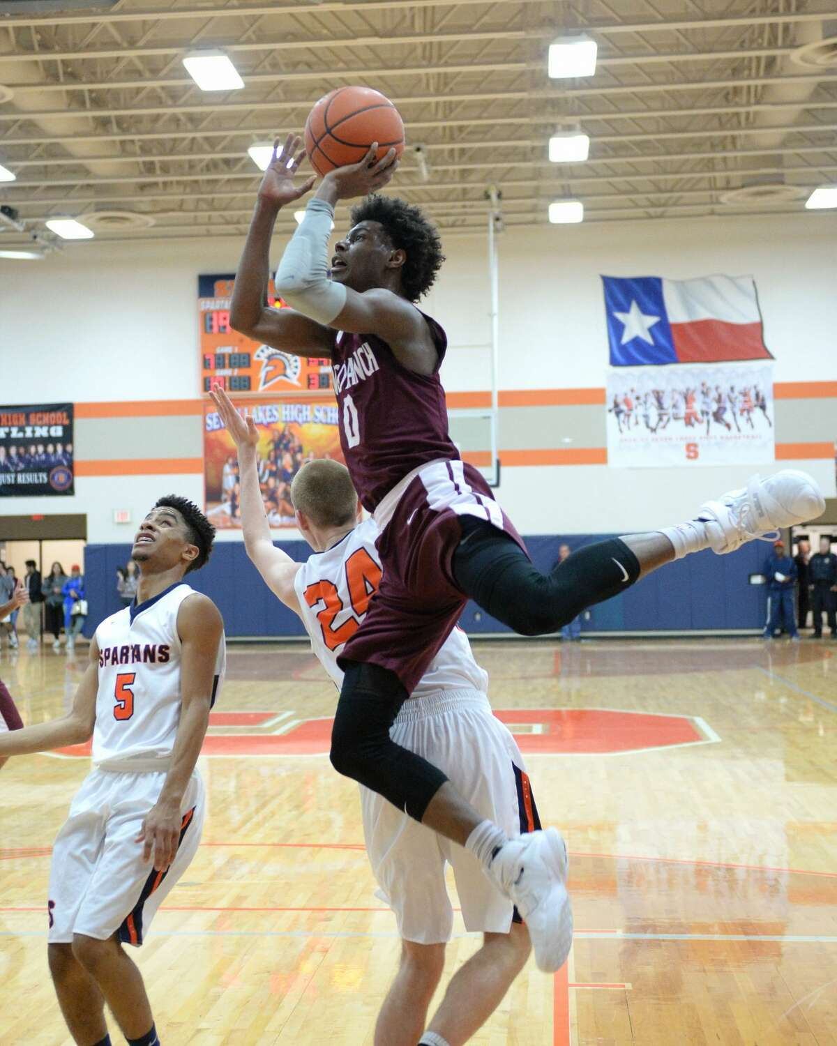 Jay Jay Chandler (0) of Cinco Ranch shoots past Jonathan Howell (24) and Logan West (5) of Seven Lakes during the first half of a boys basketball game between the Cinco Ranch Cougars and the Seven Lakes Spartans on Friday January 6, 2017 at the Seven Lakes HS, Katy, TX.