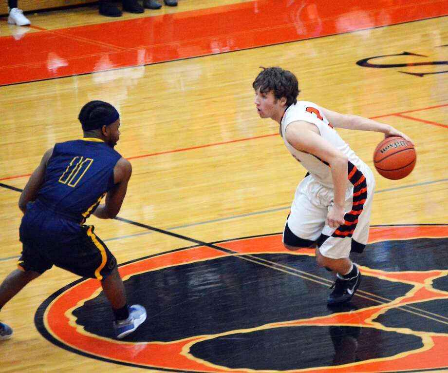 Edwardsville guard Jack Marinko, right, brings the ball up the court.