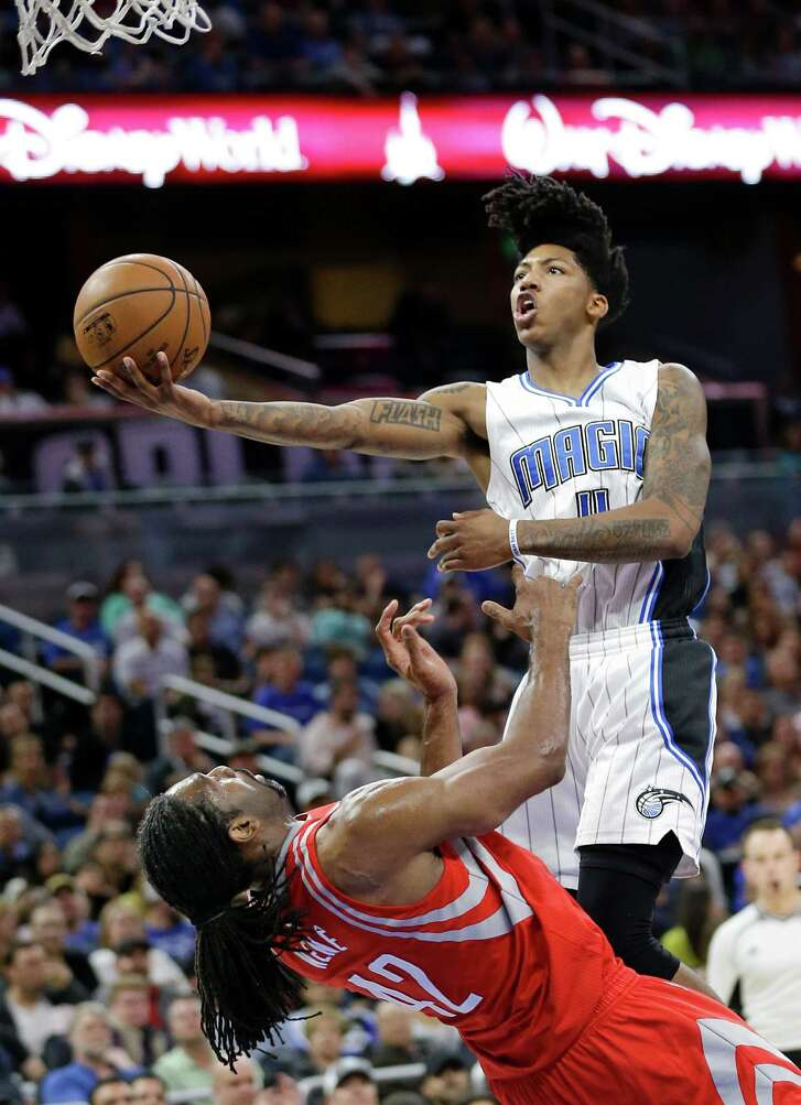 Nene, left, pays the price for trying to draw a charge against the Magic's Elfrid Payton during the Rockets' 100-93 victory at Orlando on Friday night.