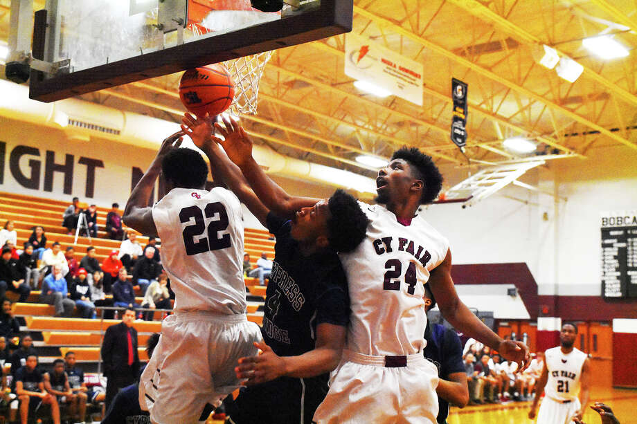 Cy Ridge sophomore guard Noah Smith is met with some defense in the form of Cy-Fair junior forward T.J. Carter (24) and freshman forward Adrian Caldwell (22). Smith was one of three Rams to finish with 12 points in the 79-73 loss to Cy-Fair Friday. Photo: Tony Gaines / HCN