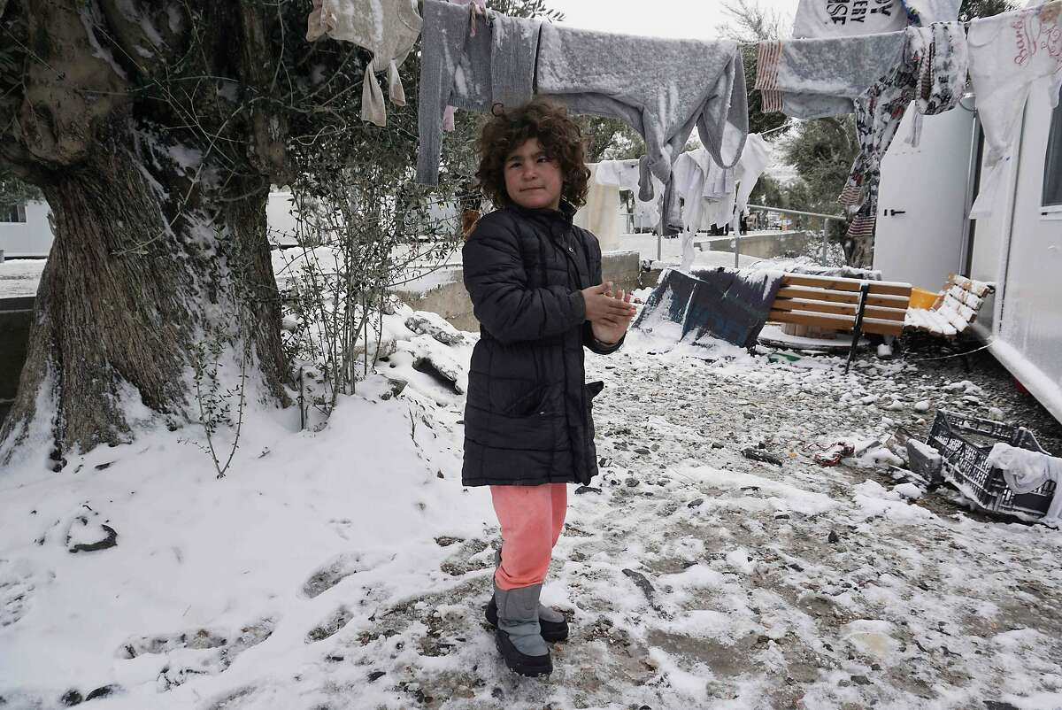 TOPSHOT - A child plays in the snow at the Kara Tepe camp on the island of Lesbos following heavy snowfalls on January 7, 2017. The number of migrants arriving in Europe by two main sea routes in 2016 plunged by almost two-thirds to 364,000 compared with the previous year, EU border agency Frontex said Friday. Frontex pointed to an EU border deal with Turkey which came into effect in March as having paved the way to a massive decline in the arrival of Syrian refugees and other migrants in Greece. / AFP PHOTO / STRSTR/AFP/Getty Images