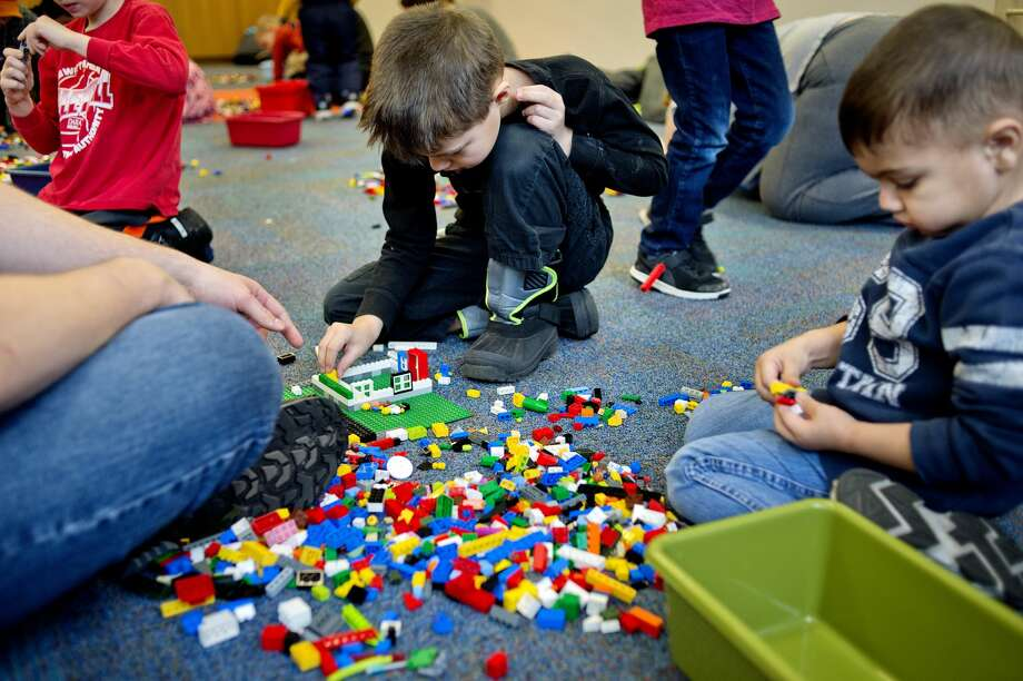 NICK KING | nking@mdn.net  Kadin Shoemaker, 7, center, his brother Carter, 3, and their father Artemis build with LEGO blocks during the LEGO @ the Library event on Saturday at the Grace A. Dow Memorial Library. The popular building blocks were available for youngsters to build and play with in the Library Story Room from 10:30 a.m. to noon. Creations made by the kids will be on display at the Youth Services Desk for the rest of the month. Photo: NICK KING | Nking@mdn.net