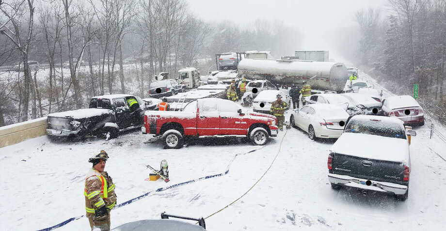A firefighter works in front of a Connecticut State Police patrol car at the scene of an pileup near Exits 20-25 that closed down I-91 Saturday, Jan. 7, 2017. A tanker truck can be seen in the background. Photo: Contributor Photo / CSP, Hearst Connecticut Media / Connecticut Post