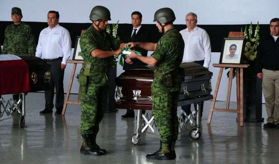 Miembros del Ejército Mexicano doblan una bandera mexicana durante la ceremonia de homenaje. Photo: Foto De Cortesía|Gobierno De Tamaulipas