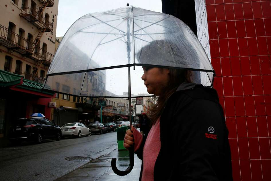 A pedestrian tries to stay dry in Chinatown Jan. 7, 2017 in San Francisco, Calif.