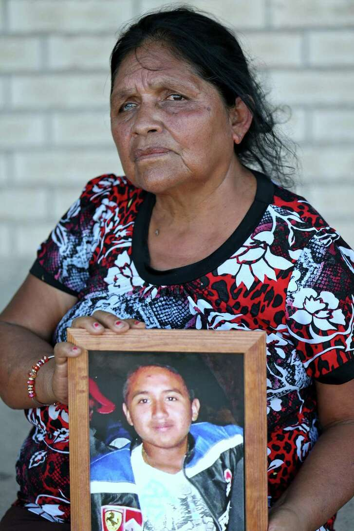 Irma Bermudes Gracia holds a portrait of her slain grandson Carlos Gracia. Sheriff's deputies found Gracia in a wrecked pickup truck in late 2014. He had been shot in the head. Gracia worked for a smuggling organization and was in and out of juvenile detention, and repatriated to Mexico.