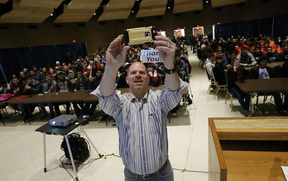 Patrick Felty, Alamo Regional Director First Robotics, takes a selfie with hundreds of students as CPS Energy helps kick off the annual FIRST Robotics competition by presenting a livestream of the event and handing out the fundamental robotics-building kits to area school teams on Saturday, Jan. 7, 2016 at La Villita Assembly Hall. Eager robotics students awaited the announcement of this year's project at the same time as all 83,000 high school students competing around the world. This year, for the first time, the project will be steampunk-related. Students have six weeks to build a robot that can handle the various tasks and challenges for this year's competition. All the efforts by the students will culminate in a competition where students can attain scholarships. The FIRST Robotics competition offers $50 million in scholarships according to the organization. (Kin Man Hui/San Antonio Express-News) Photo: Kin Man Hui, Staff / San Antonio Express-News / ©2017 San Antonio Express-News
