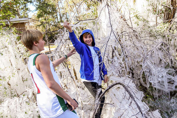 Jett Jensen and Ty Risner, both 13-years-old and from The Woodlands, explore a patch of trees that were suddenly turned into an icy tundra after a pipe broke in the freezing temperatures on Saturday, Jan. 7, 2017, near Forestgate Park.