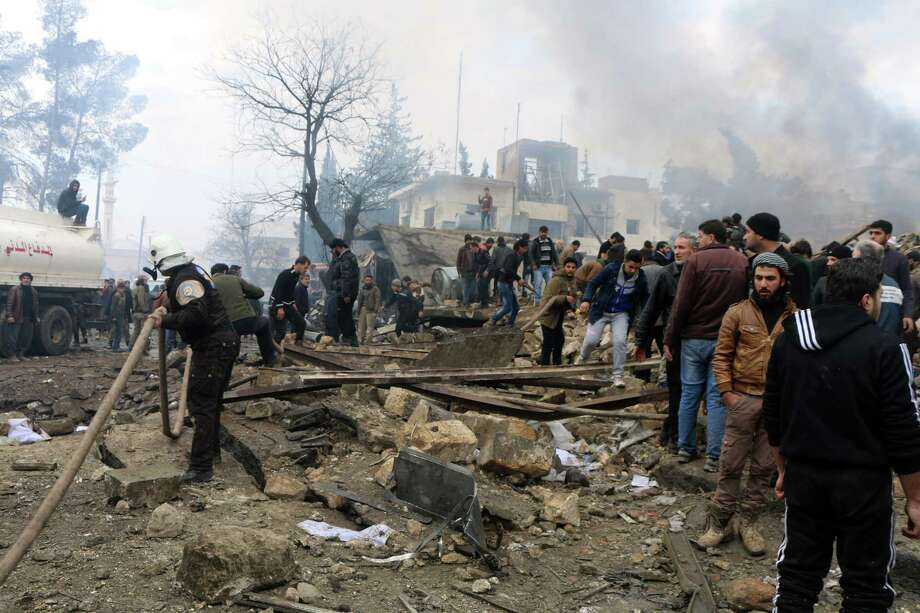 Rescue workers attend to the wreckage after a car bomb went off Saturday in a busy market in rebel-held Azzaz, Syria, near the Turkish border. Russia-brokered peace talks will be held later this month in Kazakhstan. Photo: Saif Alnajdi, UGC / Saif Alnajdi