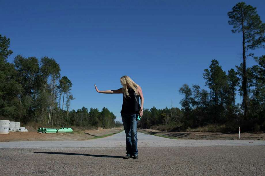Lee Ann Penton-Walker imitates the way her father used to signal cars and trucks to slow down on a residential road in front of her home and the entrance to one of the developments by Colony Ridge Land. Photo: Marie D. De Jesus, Staff / © 2016 Houston Chronicle