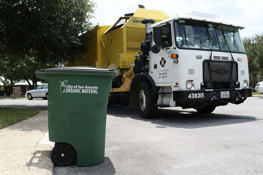 "A City of San Antonio Solid Waste Department truck picks up organic material while on its route in North Central San Antonio, Tuesday, August 18, 2015. The city program called, ""Pay as You Throw,"" offers lower rates for garbage service by letting them recycle more of their waste. Residents have the option of cutting their solid waste collection fee by choosing a smaller garbage bin and recycling more items. Photo: JERRY LARA, Staff / San Antonio Express-News / © 2015 San Antonio Express-News"