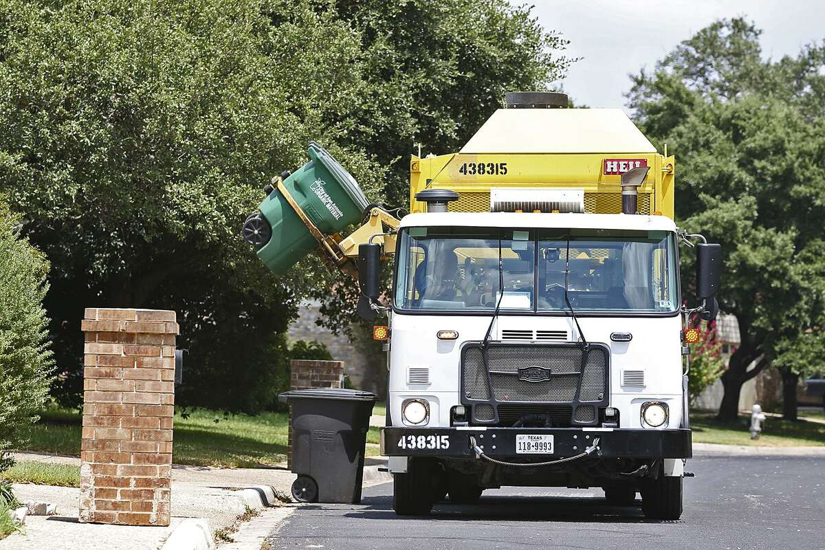 """A City of San Antonio Solid Waste Department truck picks up organic material while on its route in North Central San Antonio, Tuesday, August 18, 2015. The city program called, """"Pay as You Throw,"""" offers lower rates for garbage service by letting them recycle more of their waste. Residents have the option of cutting their solid waste collection fee by choosing a smaller garbage bin and recycling more items."""