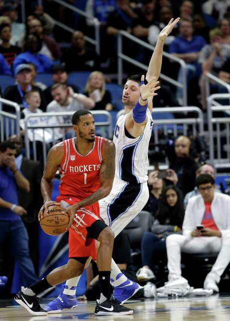 The Rockets' Trevor Ariza looks for a teammate when the Magic's Nikola Vucevic blocks his way Friday. The Rockets padded their win streak to seven. Photo: John Raoux, STF / Copyright 2017 The Associated Press. All rights reserved.