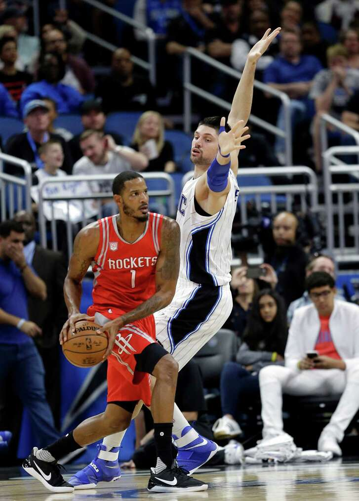 The Rockets' Trevor Ariza looks for a teammate when the Magic's Nikola Vucevic blocks his way Friday. The Rockets padded their win streak to seven.