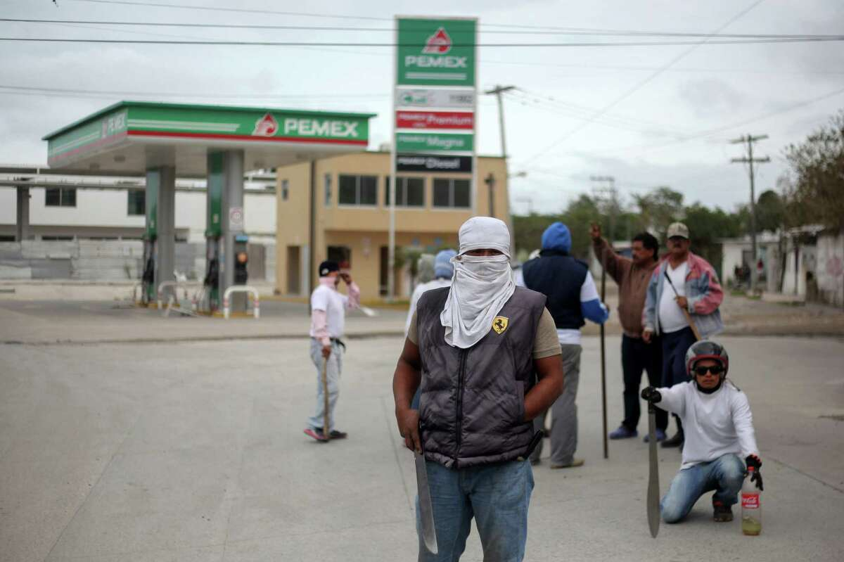Masked men stand guard in front of a gas station in Veracruz, Mexico, Saturday, Jan. 7, 2017. As looting as largely subsided in Mexico, following a 20 percent hike in gasoline prices, neighborhoods in affected é¡reas have taken to guarding themselves from potential looters. (AP Photo/Felix Marquez)