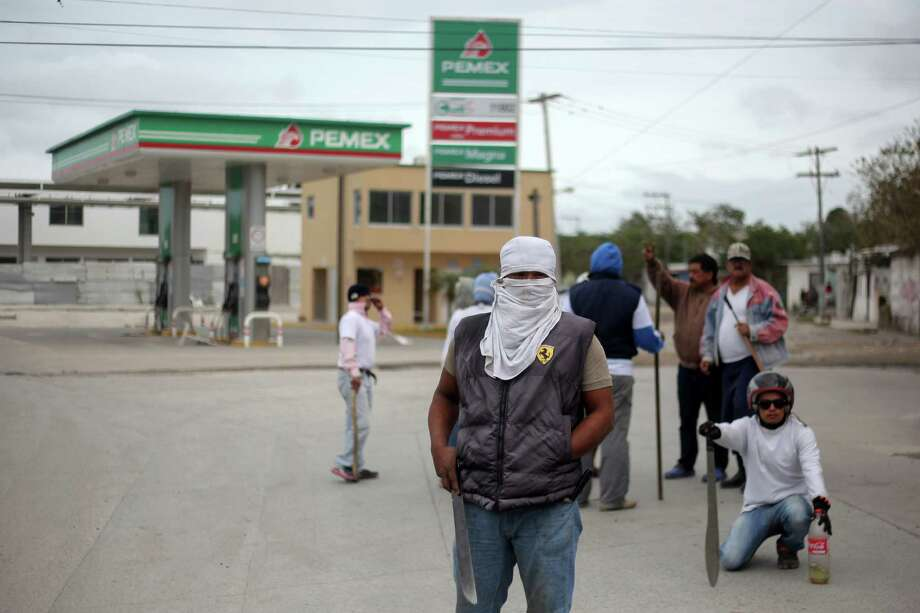 Masked men stand guard in front of a gas station in Veracruz, Mexico, Saturday, Jan. 7, 2017. As looting as largely subsided in Mexico, following a 20 percent hike in gasoline prices, neighborhoods in affected é¡reas have taken to guarding themselves from potential looters. (AP Photo/Felix Marquez) Photo: Felix Marquez, STR / Copyright 2017 The Associated Press. All rights reserved.