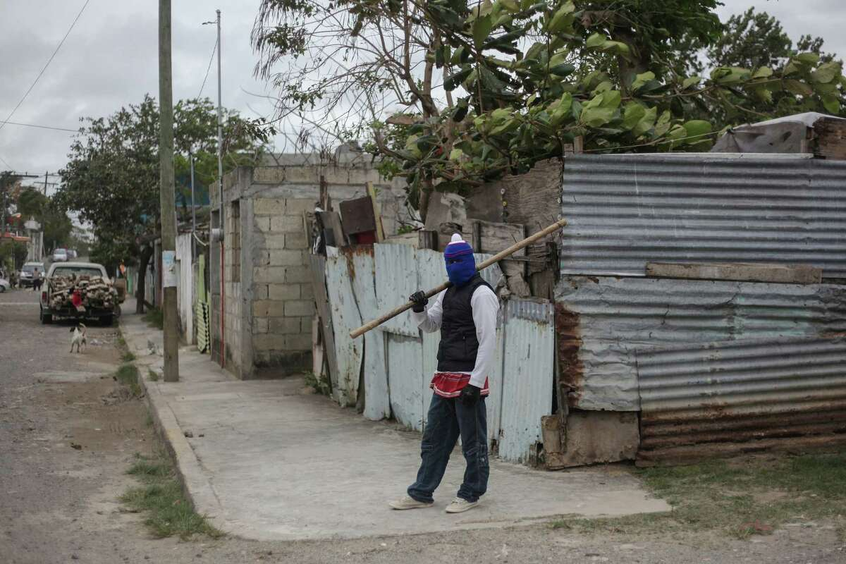 A masked man stands guard at a neighborhood in Veracruz, Mexico, Saturday, Jan. 7, 2017. As looting as largely subsided in Mexico, following a 20 percent hike in gasolina prices, neighborhoods in affected é¡reas have taken to guarding themselves from potential looters. (AP Photo/Felix Marquez)