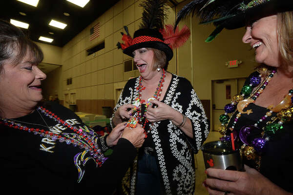 From left, long-time friends Jerri McCown, JoJo James, and Debi Tamez joke with one another as they check out their Mardi Gras coin necklaces and enjoy the festivities at the fifth annual Beans and Jeans fundraising party held Saturday night at the Bob Bowers Civic Center in Port Arthur. The event coincides with Three Kings' Day, which officially ends the Christmas season and kicks off the start for Mardi Gras season. Revelers got in the spirit, celebrating with red beans and rice, king cake and musical entertainment by Electric Circus as the Krewes for this year's 25th Mardi Gras of Southeast Texas were introduced. The season reaches its climax with the weekend-long party and parades in downtown Port Arthur that begins February 23. Photo taken Saturday, January 7, 2017 Kim Brent/The Enterprise