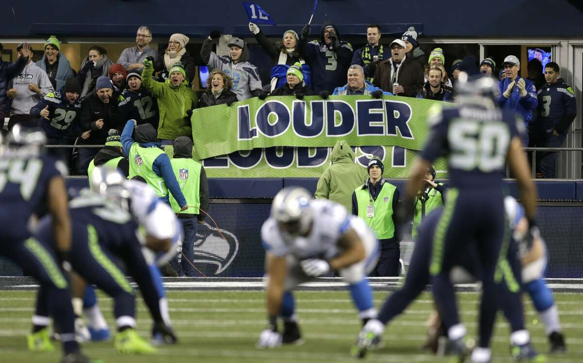 Seattle Seahawks fans yell behind a banner that reads