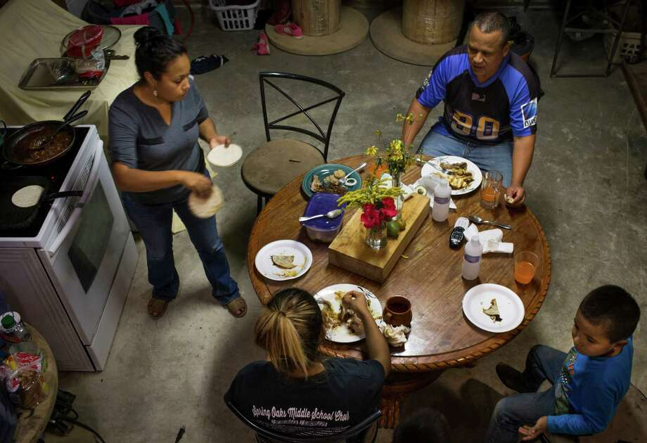Carlos Macedo, 44, Janet Macedo, 33, Isaac Macedo, 5, and Alexandra Campos, 14, gather for dinner at their home in the Montebello Subdivision in Cleveland, Monday, Oct. 17, 2016. The family moved into a lot they financed with the developers of the subdivision on October 2015 and started building a new house while living in a mobile home in the front yard. Janet and Carlos Macedo work together about 50 hours a week servicing Direct TV customers as contractors. Photo: Marie D. De Jesus, Houston Chronicle / © 2016 Houston Chronicle