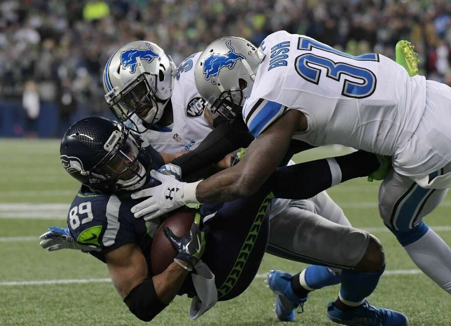 Seahawks wide receiver Doug Baldwin (89) is brought down by Detroit Lions strong safety Rafael Bush (31) and strong safety Tavon Wilson (32) during the second half. Photo: Kirby Lee/USA Today Sports