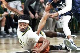 Siena's #15 Nico Clareth, left, and Saint Peter's #20 Chazz Patterson chase a loose ball during Saturday's game at the Times Union Center Jan. 7, 2017 in Albany, NY.  (John Carl D'Annibale / Times Union)