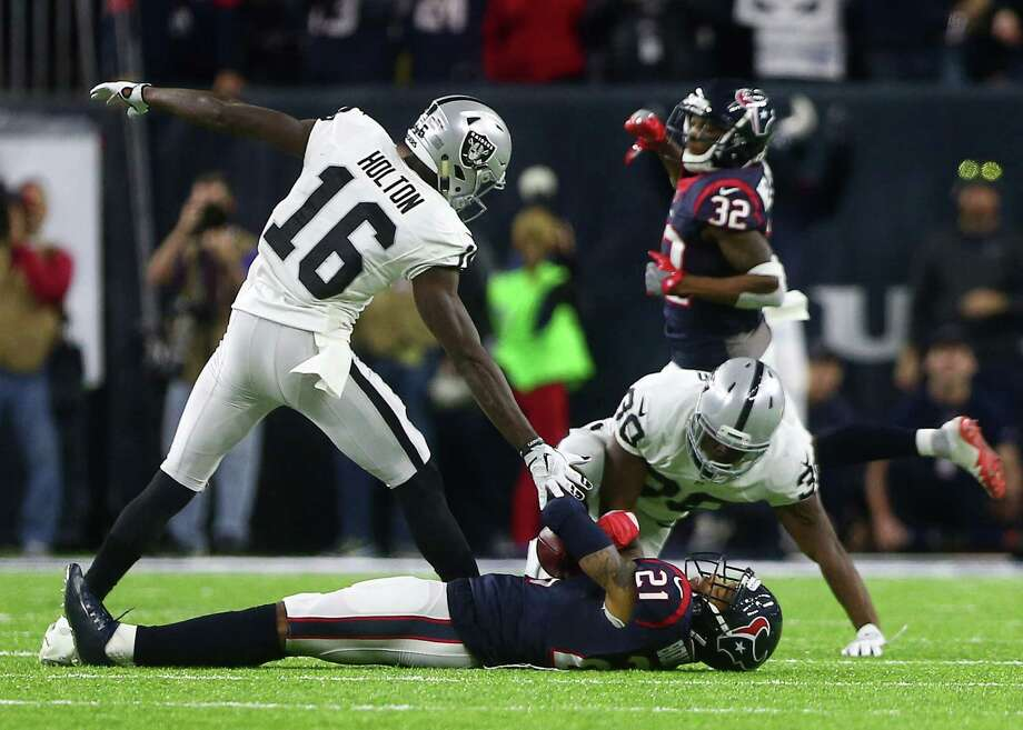 Houston Texans cornerback A.J. Bouye (21) is tagged down by Oakland Raiders wide receiver Johnny Holton (16) and defensive back SaQwan Edwards (30) after he intercepted a pass to seal the Oakland Raiders loss to the Houston Texans in an AFC Wild Card Playoff game at NRG Stadium Saturday, Jan. 7, 2017, in Houston. ( Jon Shapley / Houston Chronicle ) Photo: Jon Shapley, Staff / © 2015  Houston Chronicle