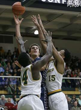 Saint Mary's center Evan Fitzner, center, shoots against San Francisco guard Charles Minlend (14) and forward Nate Renfro (15) during the first half of an NCAA college basketball game in San Francisco, Saturday, Jan. 7, 2017. (AP Photo/Jeff Chiu)