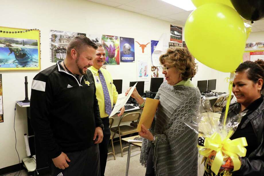 Joe Roberts, left, is surprised by Liberty ISD Education Foundation Directors Margaret Gardzina and Sandra Garcia.Liberty High School Principal Dr. Chad Barrett looks on as his teacher receives notification he has won a grant. Photo: David Taylor