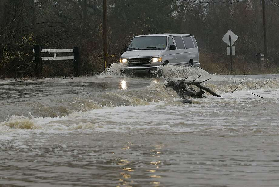 A van drives through flooded water on Green Valley Road in Graton in Sonoma County on Saturday. Photo: Jeff Chiu, Associated Press