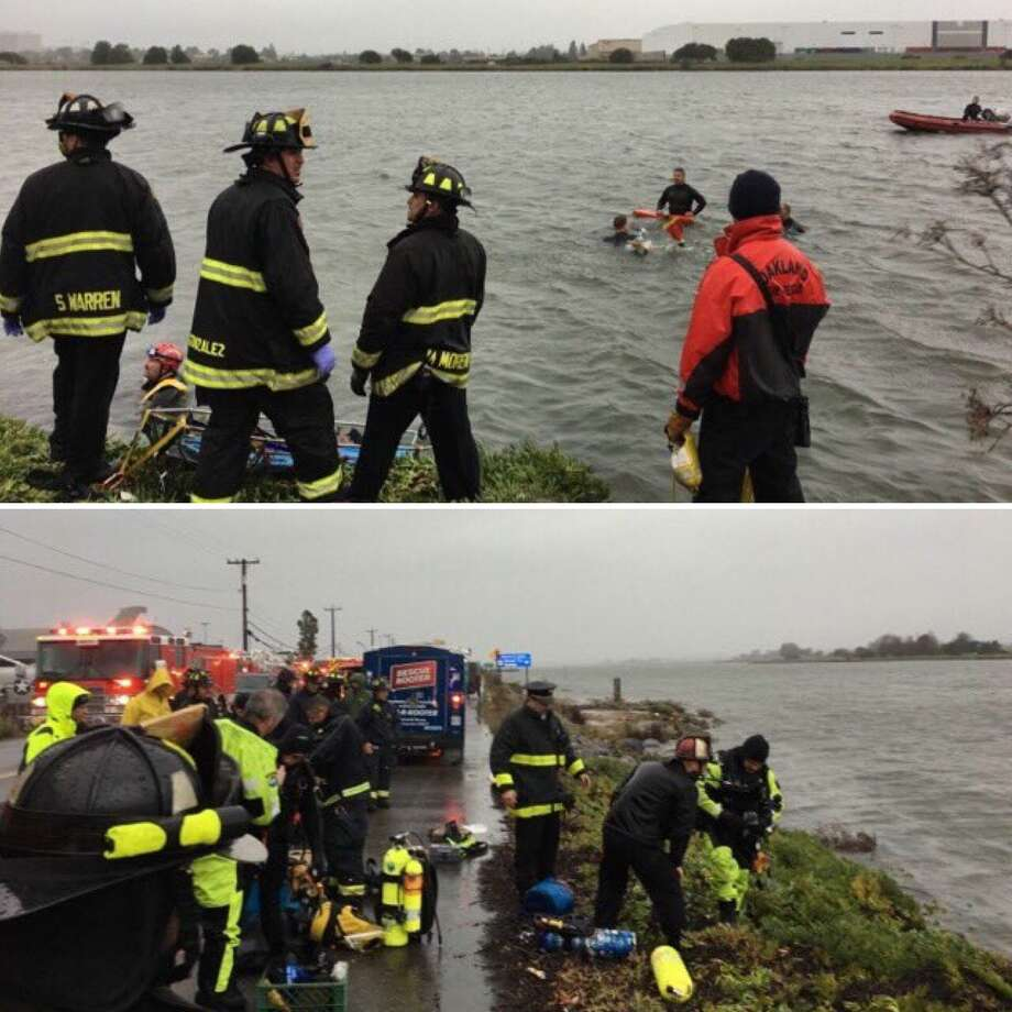 Rescue swimmers and divers were dispatched to the Oakland estuary near Oakland International Airport around 8:30 a.m. following reports of two people trapped in a car that went into the water Sunday morning. Photo: @Oaklandfirelive / /