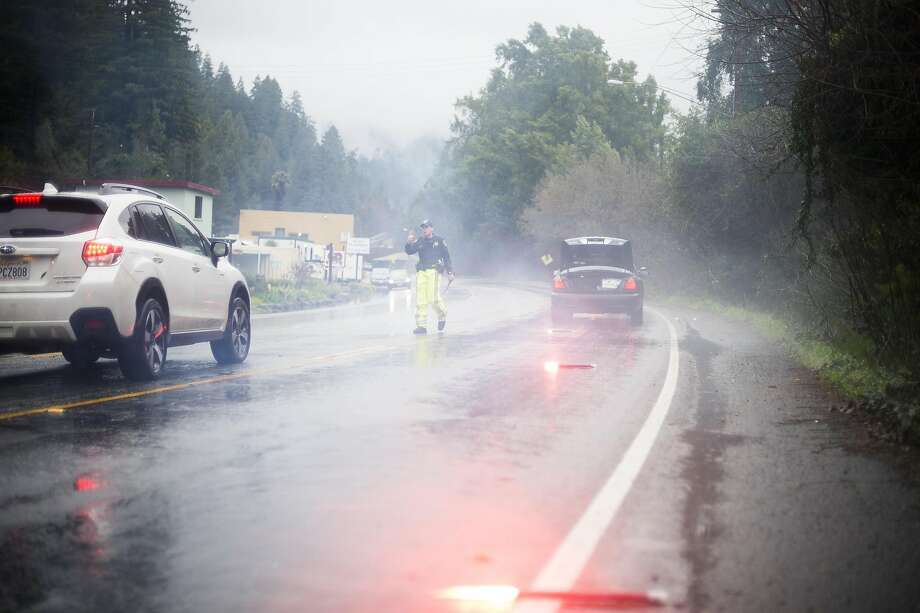 Santa Rosa CHP officer Ken Enger directs traffic around a car, which skidded off of the road during flooding in Sonoma County in January. Photo: Brian L. Frank, Special To The Chronicle
