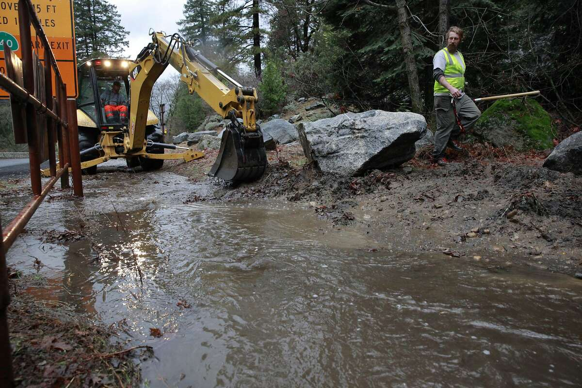 Jeremy Brown, (right) helps to clear debris at the intersection of highways 120 and 140 after heavy rains in Yosemite National Park, Ca., on Sunday Jan. 8, 2017, which is currently under a flash flood watch.