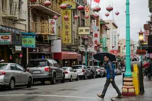 A man walks across Grant Street in Chinatown during a rainstorm in San Francisco, Calif., on Sunday, Jan. 8, 2017.