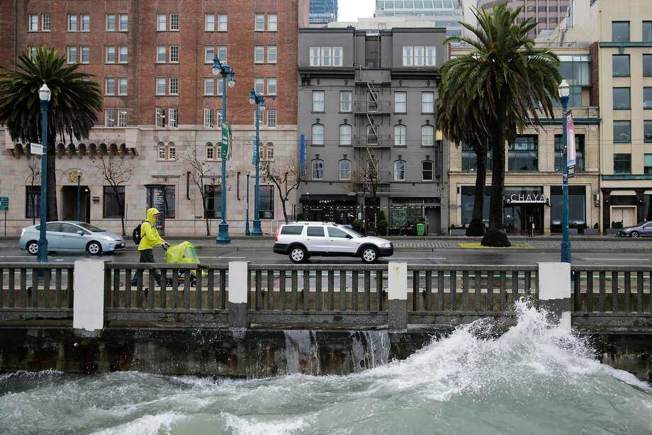 Graeme Paterson walks along the Embarcadero during a rainstorm in San Francisco, Calif., on Sunday, Jan. 8, 2017. Photo: Gabrielle Lurie, The Chronicle