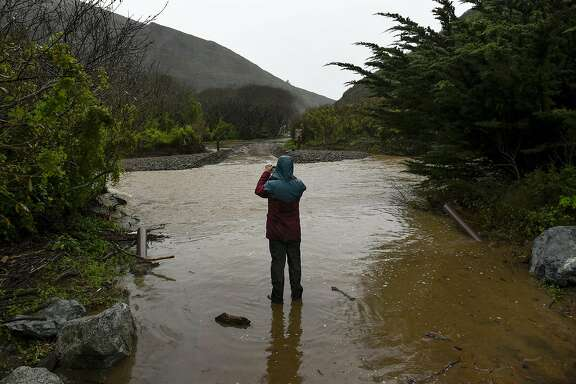 Chronicle reporter Evan Sernoffsky takes a picture of flooding that washed out the road leading to Pfeiffer Beach  in Big Sur, CA, on Sunday, January 8, 2017.
