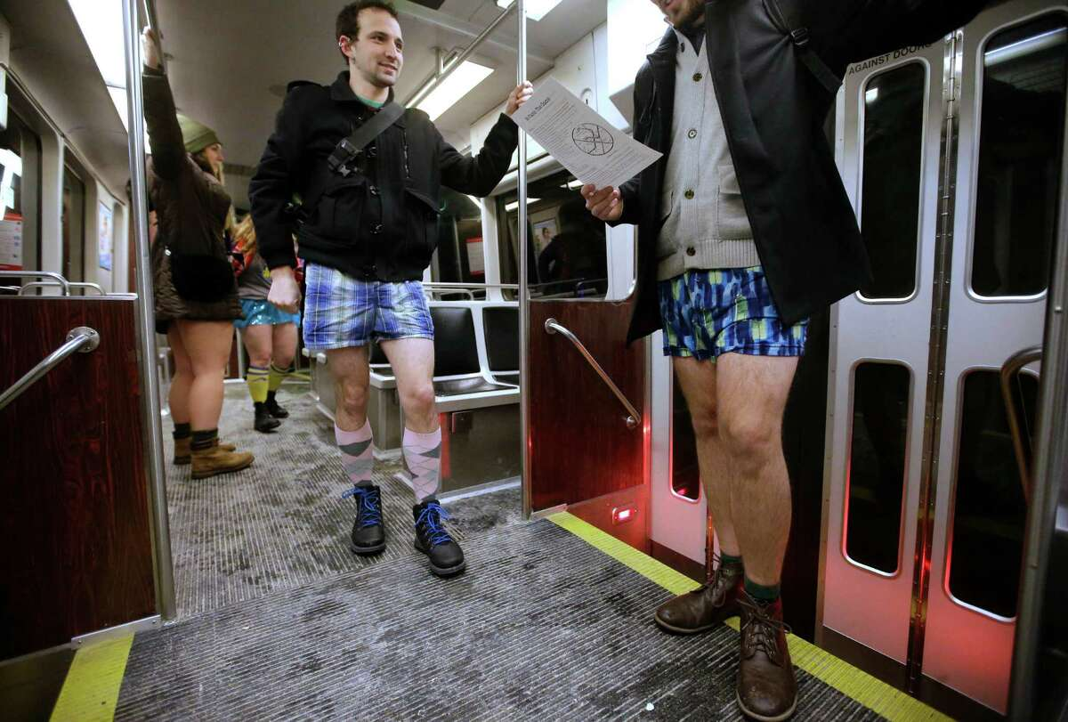 Steven Blomquist, of Somerville, Mass., center, speaks with Tim Lewis, of Boston, right, while wearing no pants as they ride a subway train during the event
