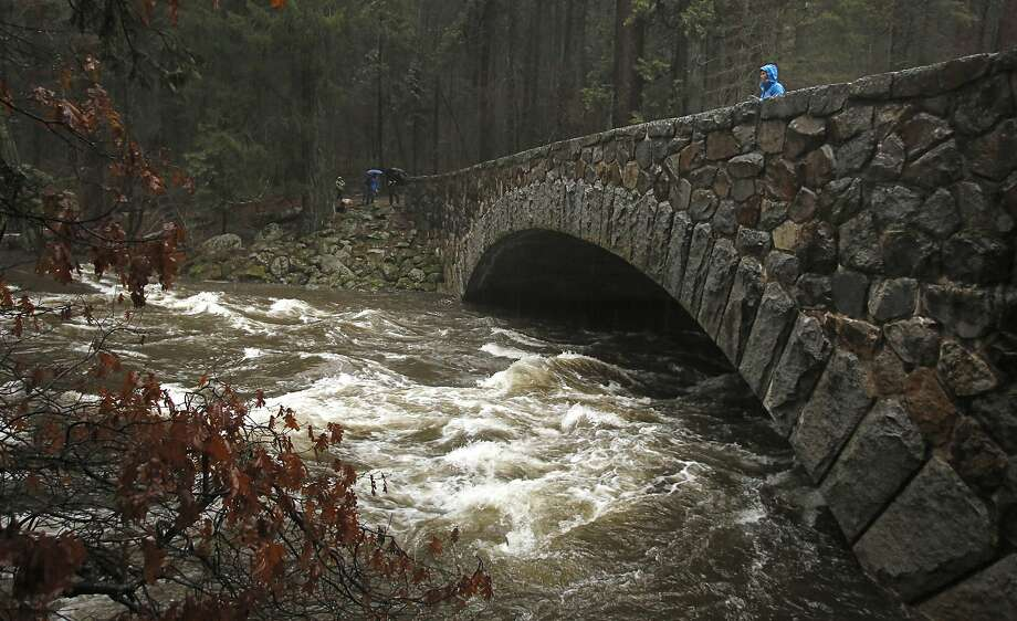 Andrea Castillo watches water flow heavily down the Merced River at the Pohono Bridge as it steadily rises throughout the day in Yosemite National Park, Calif., Sunday, Jan. 8, 2017. Stranded motorists were pulled from cars stuck on flooded roads as heavy rains from a massive winter storm moved into Northern California. (AP Photo/Gary Kazanjian) Photo: Gary Kazanjian, Associated Press