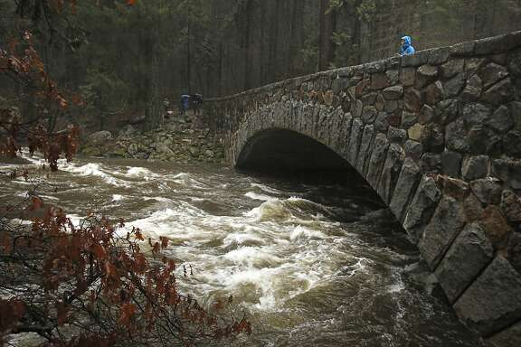 Andrea Castillo watches water flow heavily down the Merced River at the Pohono Bridge as it steadily rises throughout the day in Yosemite National Park, Calif., Sunday, Jan. 8, 2017. Stranded motorists were pulled from cars stuck on flooded roads as heavy rains from a massive winter storm moved into Northern California. (AP Photo/Gary Kazanjian)