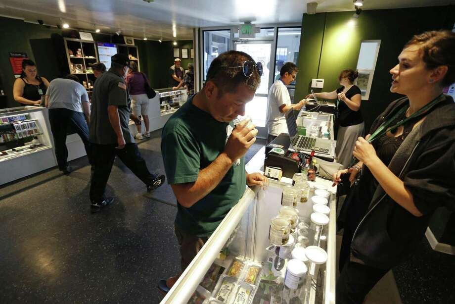 Customers shop for marijuana inside a recreational marijuana store in Denver. Sen. Elizabeth Warren, D-Mass., is leading a new effort to make sure vendors working with marijuana businesses don't have their banking services taken away. Photo: Associated Press /File Photo / Copyright 2016 The Associated Press. All rights reserved. This material may not be published, broadcast, rewritten or redistribu