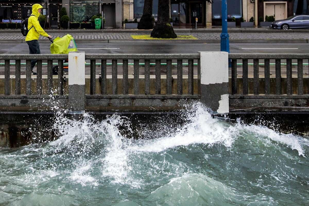 Graeme Paterson walks along the Embarcadero during a rainstorm in San Francisco on Sunday, Jan. 8, 2017.