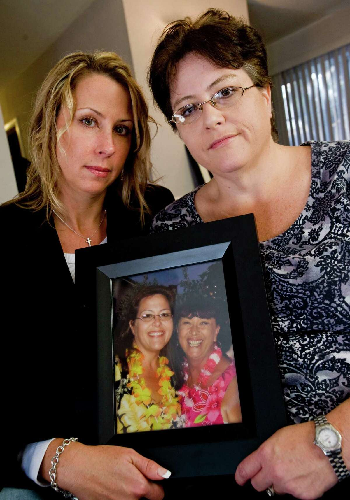 Cary Ussery, right, and her sister Kimberley Eggleston hold a photo of their mother, Linda Ware, right, and Cary. Ware, who committed suicide in Orange Country, Calif., had been taking the drug Chantix, a drug that fights nicotine addiction.