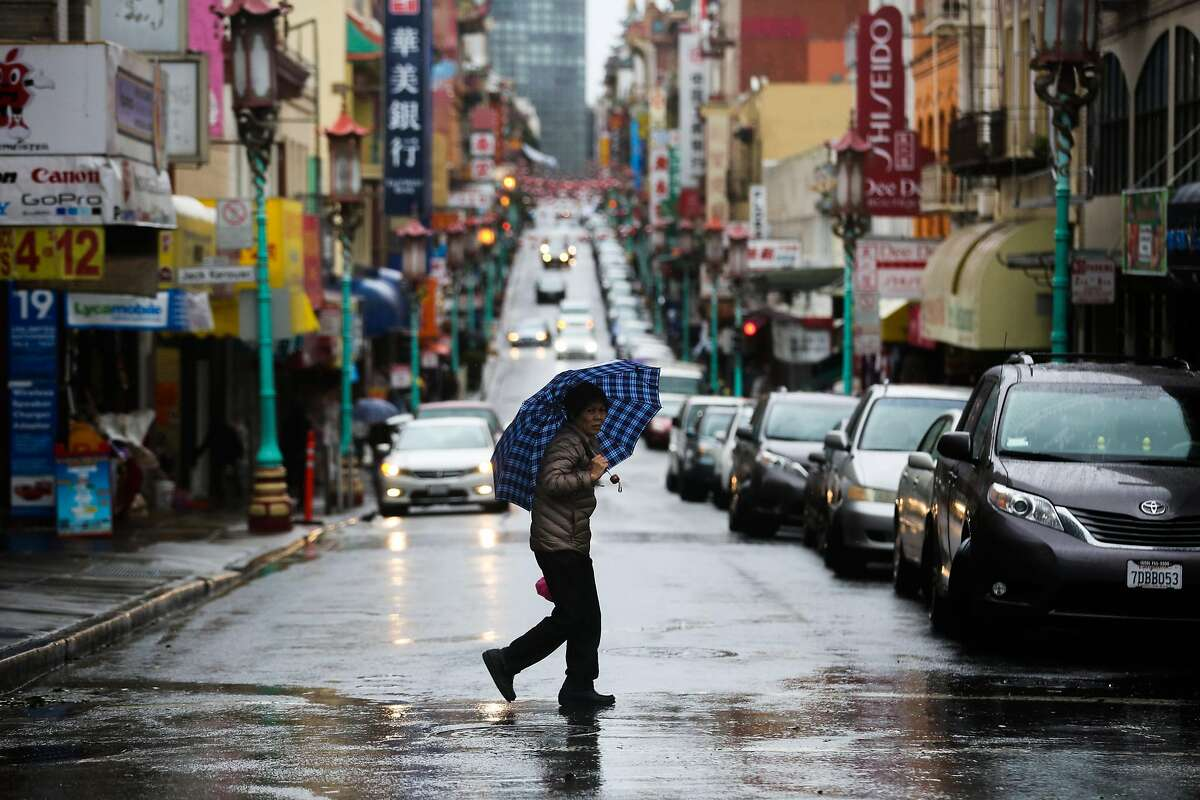 A pedestrian crosses the street during a rainstorm in San Francisco, Calif., on Sunday, Jan. 8, 2017.