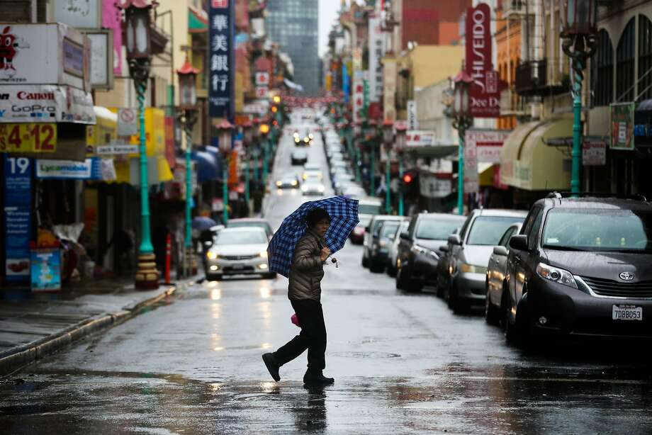 A pedestrian crosses the street during a rainstorm in San Francisco on Sunday. Photo: Gabrielle Lurie, The Chronicle