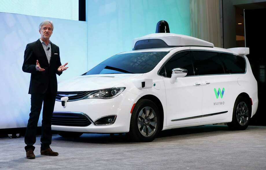 John Krafcik, CEO of Waymo, the autonomous vehicle company created by Google's parent company, Alphabet introduces a Chrysler Pacifica hybrid outfitted with Waymo's own suite of sensors and radar at the North American International Auto Show in Detroit, Sunday, Jan. 8, 2017. (AP Photo/Paul Sancya) Photo: Paul Sancya, STF / Copyright 2017 The Associated Press. All rights reserved.