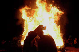 Genevieve Brassard, left, and Jacob Wills take a photo as Christmas trees burn during the annual Burning of the Greens at St. Mark's Episcopal Church on Sunday evening. The event was started in the 1950s by parishioner Seth Birdwell to celebrate the end of the Christmas season and beginning of the Epiphany season.  Photo taken Sunday 1/8/17 Ryan Pelham/The Enterprise