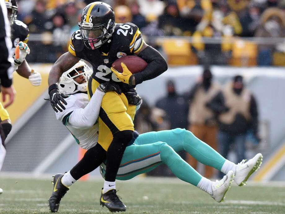 Pittsburgh Steelers running back Le'Veon Bell (26) runs throw a tackle by Miami Dolphins free safety Bacarri Rambo (30) during the first half of an AFC Wild Card NFL football game in Pittsburgh, Sunday, Jan. 8, 2017. (AP Photo/Don Wright) Photo: Don Wright, FRE / FR87040 AP